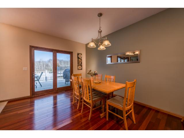 Informal dining area off the living room with cherry wood flooring and a large composite deck overlooking the state/city land. You feel like you own 100s of acres