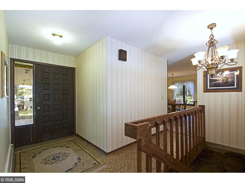 Large foyer with closet and open staircase.