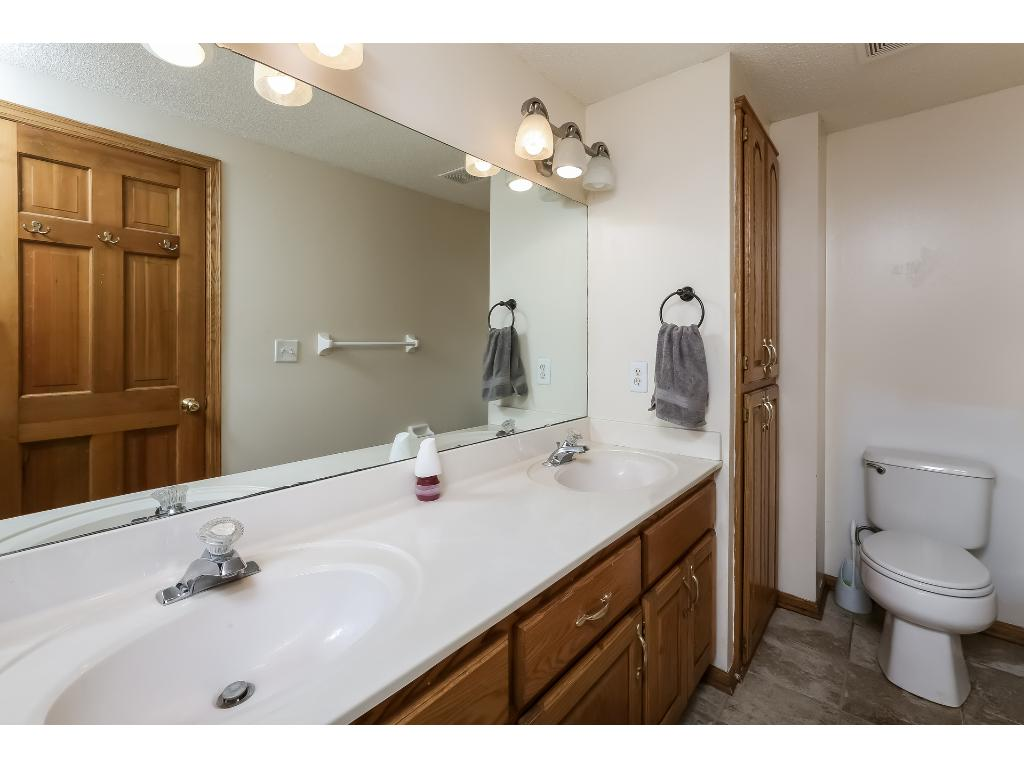 Lower level bathroom with double vanity and tub/shower.