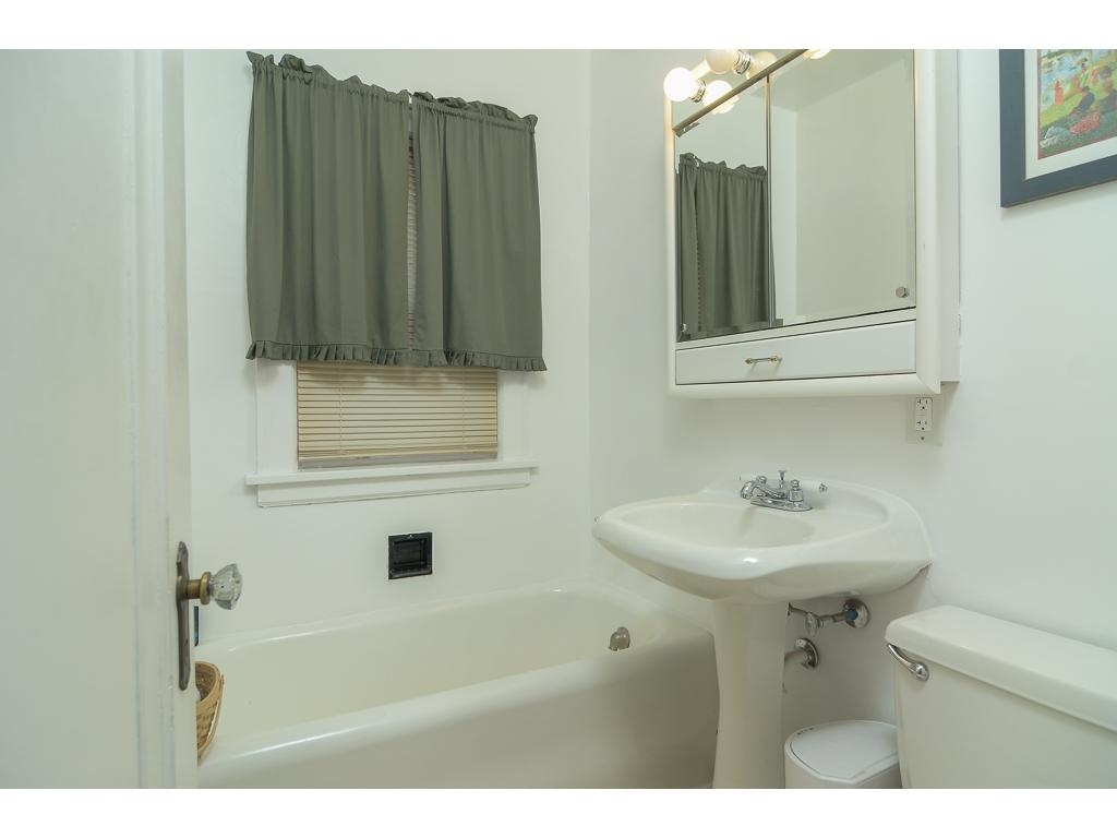 Main level full bath tucked between two bedrooms.