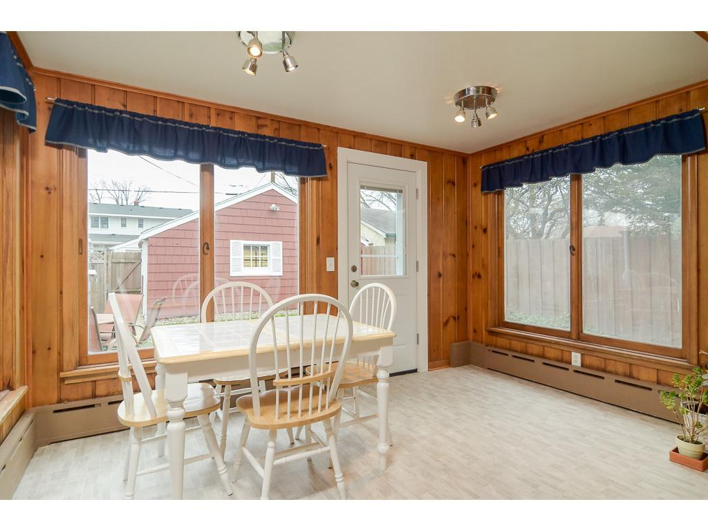 Large back informal dining room has three sides of windows overlooking the courtyard-like yard