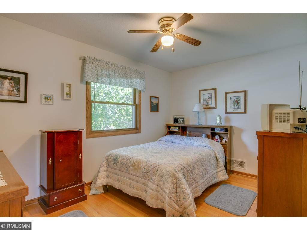 The main level master bedroom has hardwood floors, a ceiling fan and great natural light.