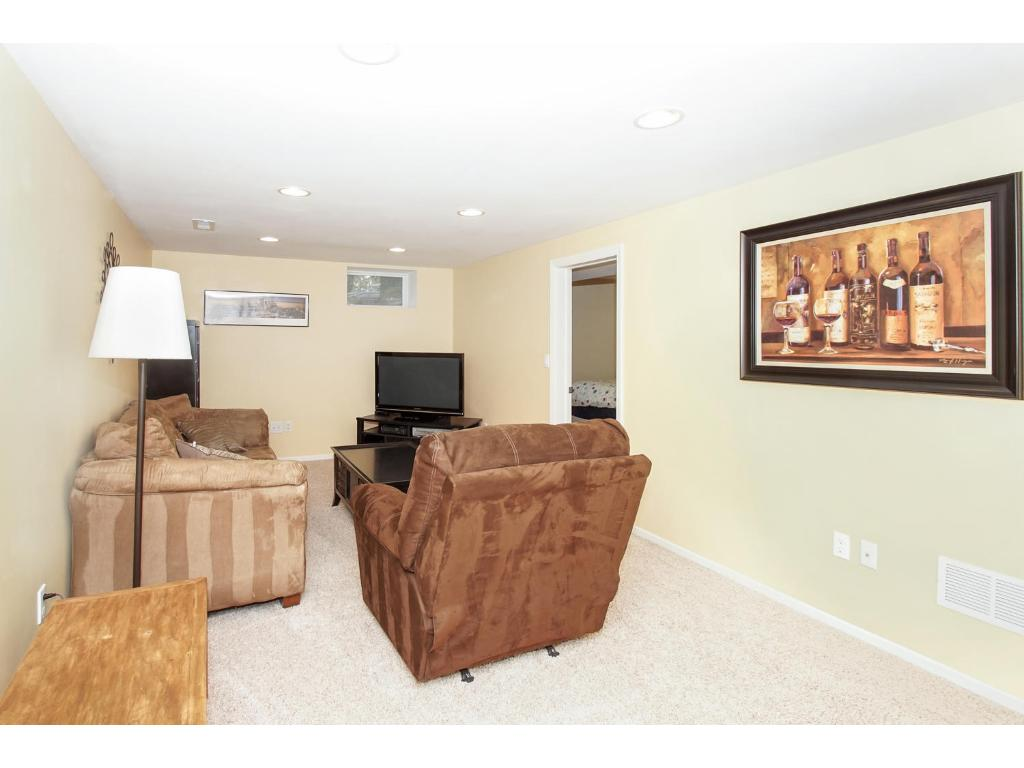 Bright updated basement with recessed lighting and white trim.