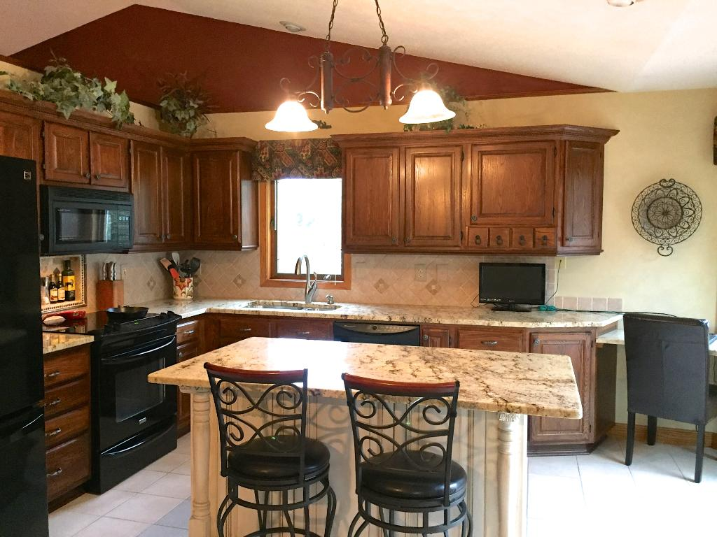 Updated kitchen features, Brazilian granite countertops, crown moulding and stylish backsplash.