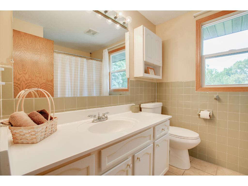 Upper level full bathroom with tile floor/surround, and long vanity.