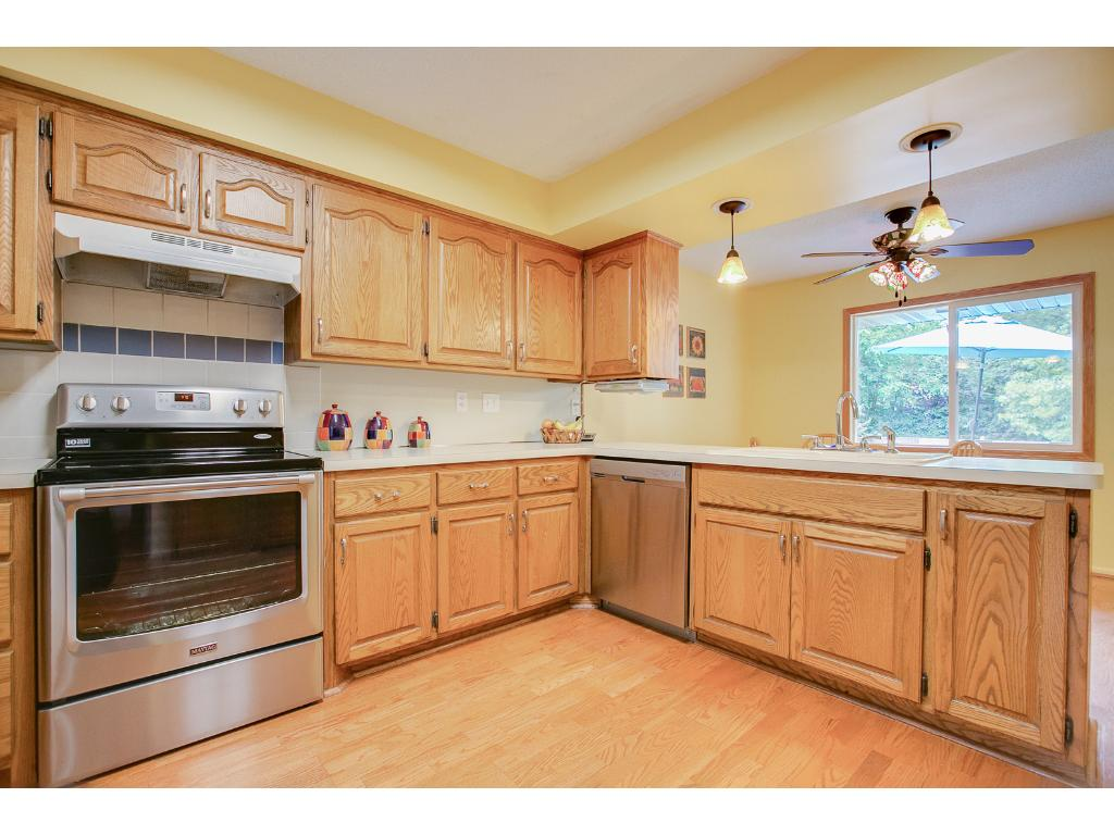 The open kitchen and dining room features stainless steel oven and dishwasher, oversized refrigerator and deep double sink.