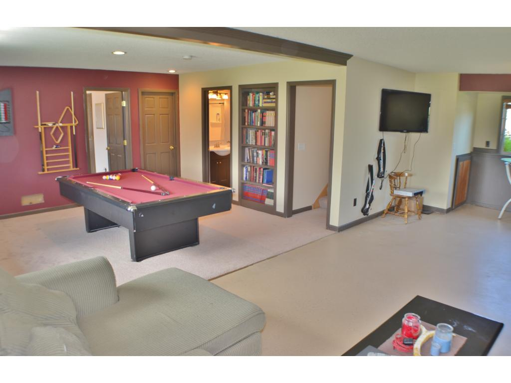 Lower level game area with pool table and dart board.