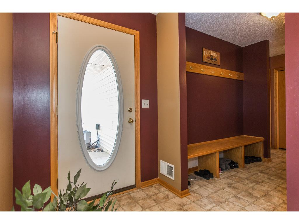 Spacious entry with coat rack and bench in addition to a walk-in closet and half bath in entry