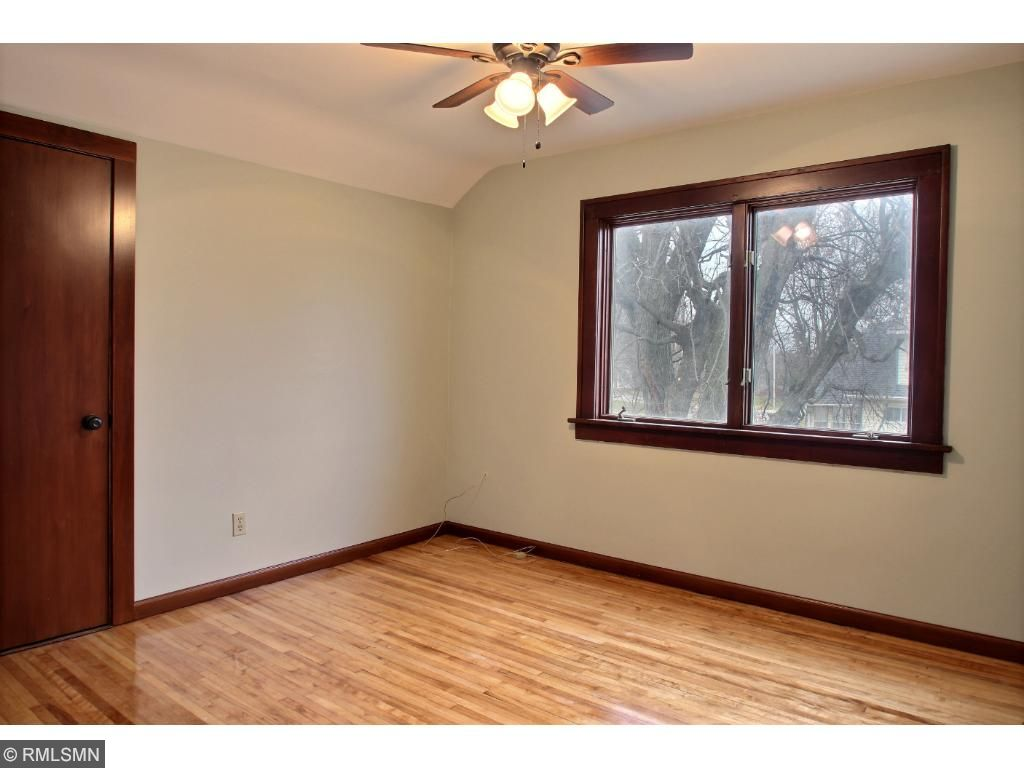 The upper level has three bedrooms, a completely renovated full bathroom and a large storage closet.  The flooring has been refinished and absolutely sparkles and shines! This is a picture of the larger upper level bedroom.