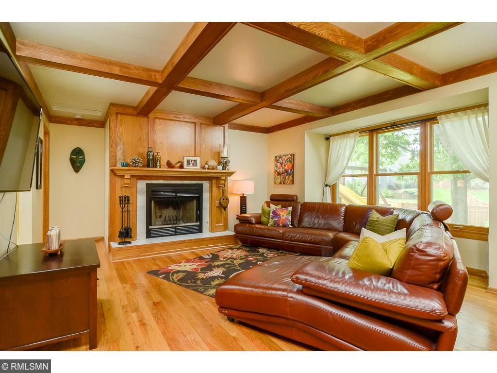 This warm coffered ceiling family room features a wood burning fireplace