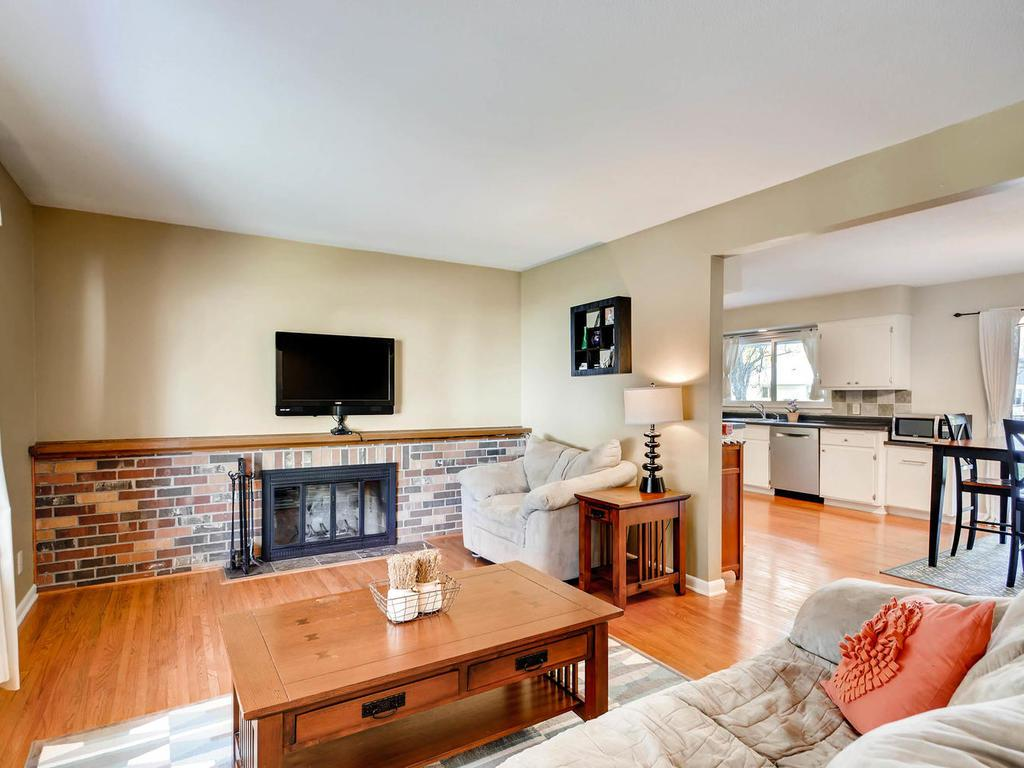 Living room has wood burning fireplace and beautiful views of the front yard.