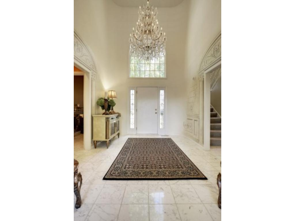A beautiful Crystal Chandelier suspended over this large front entry foyer.