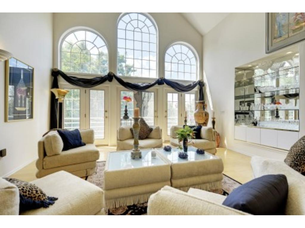 Living Room with a Two Story Vaulted Ceiling and High Arched Windows, French Doors and Hardwood Floor.