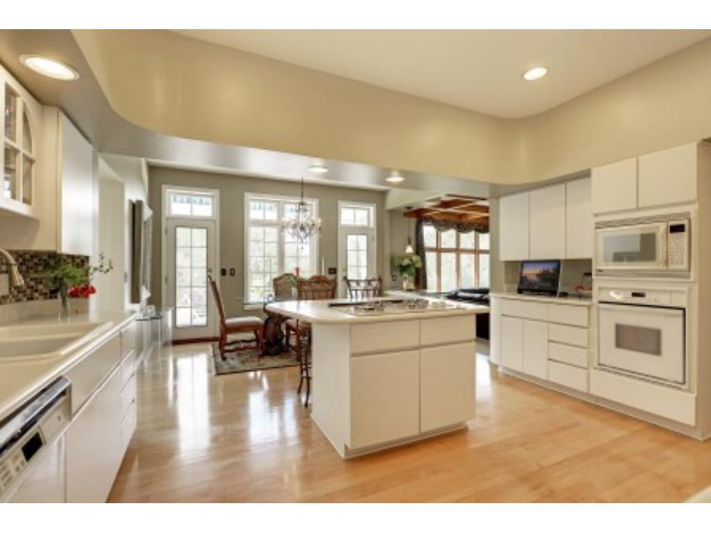 Gourmet Kitchen with Center Island, Hardwood Floor and Informal Dining Area with French Doors to Outside Deck.