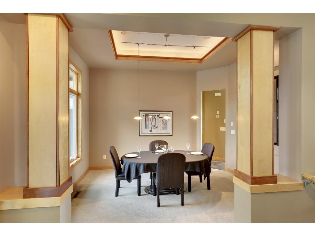 The formal dining room features square birch pillars with cherry accents, a modern light fixture, accent lighting, and a niche for art work.