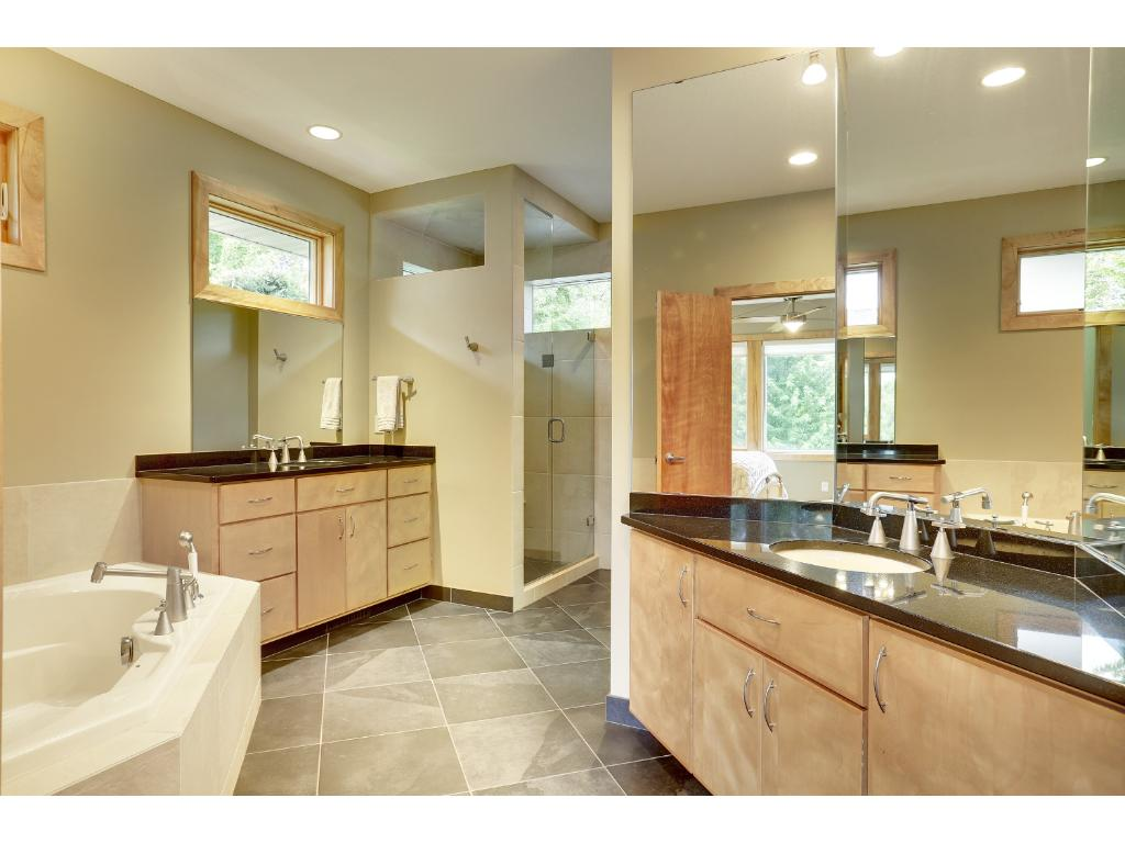 The spacious master bath includes a heated tile floor, his and her sinks with granite counters and modern fixtures. A soaking tub is elegantly separated from the tile shower with glass door and rain showerhead.