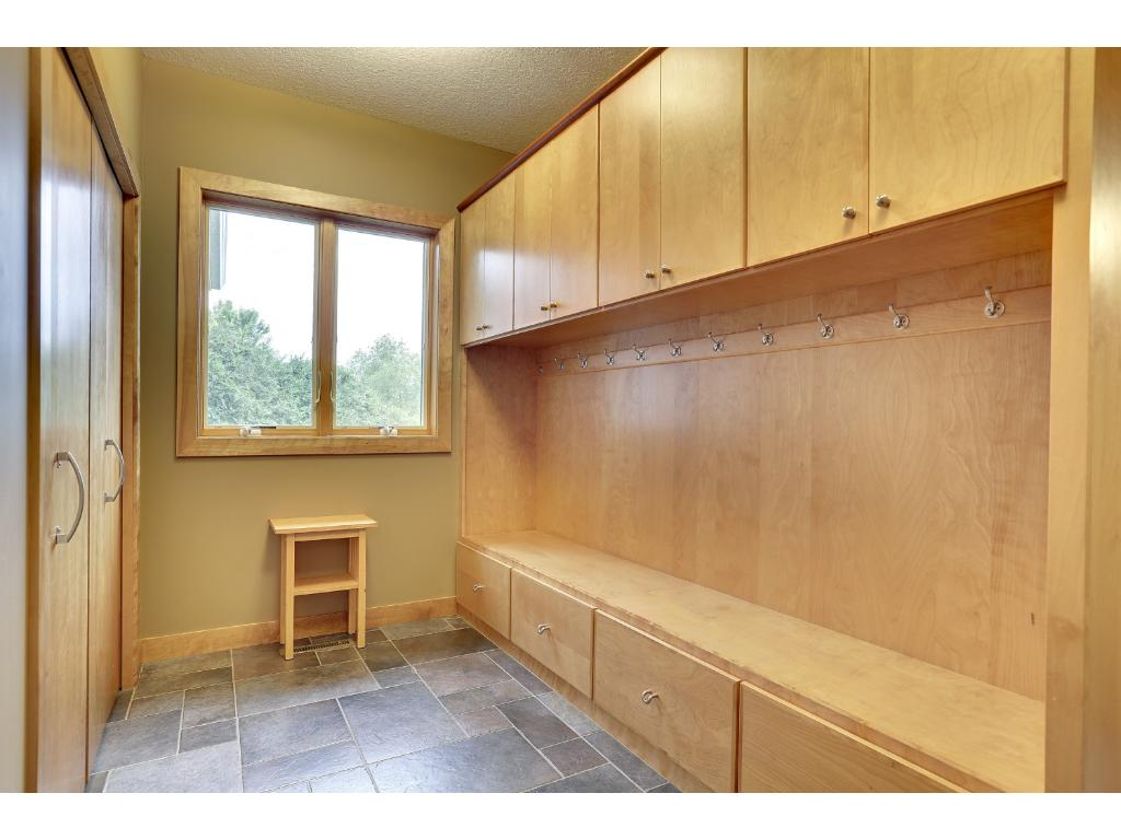 Large mudroom with built-in bench, lockers and closet.