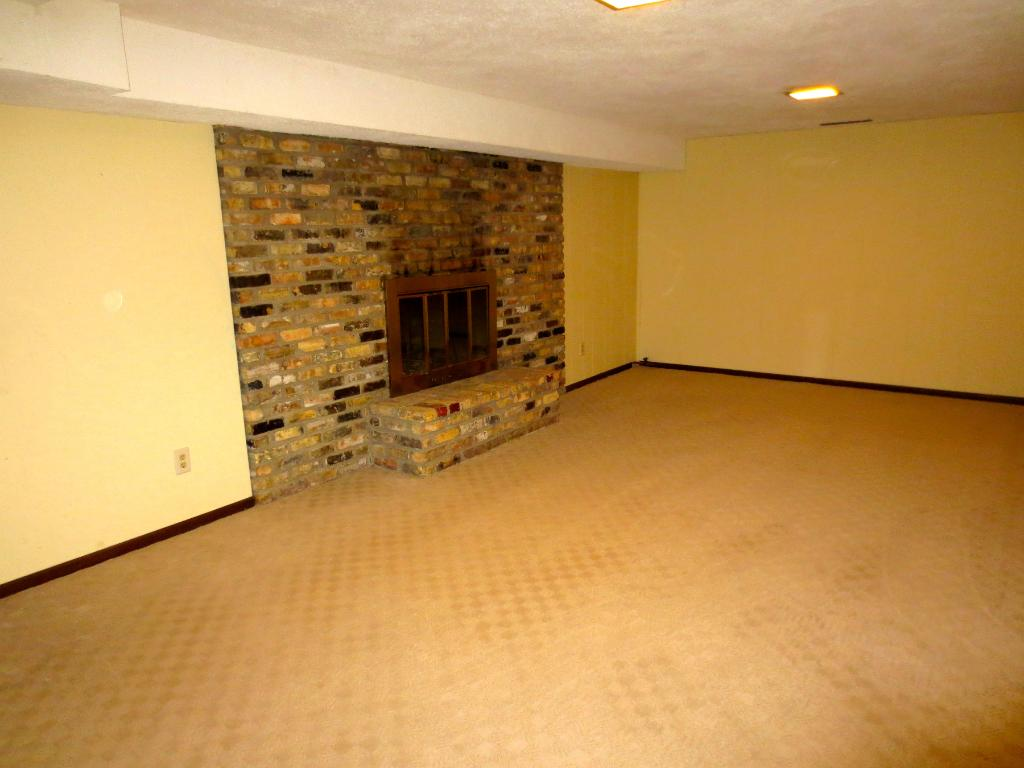 The rec room in the lower level with the other side of the 2 sided fireplace.