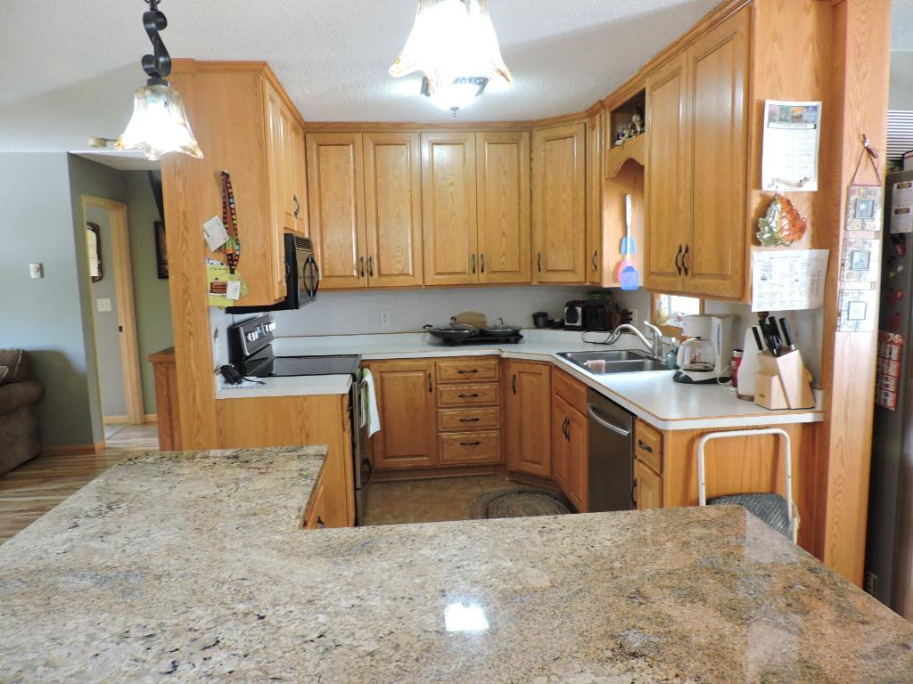 Kitchen w/lots of oak cabinets and stainless steel appliances.