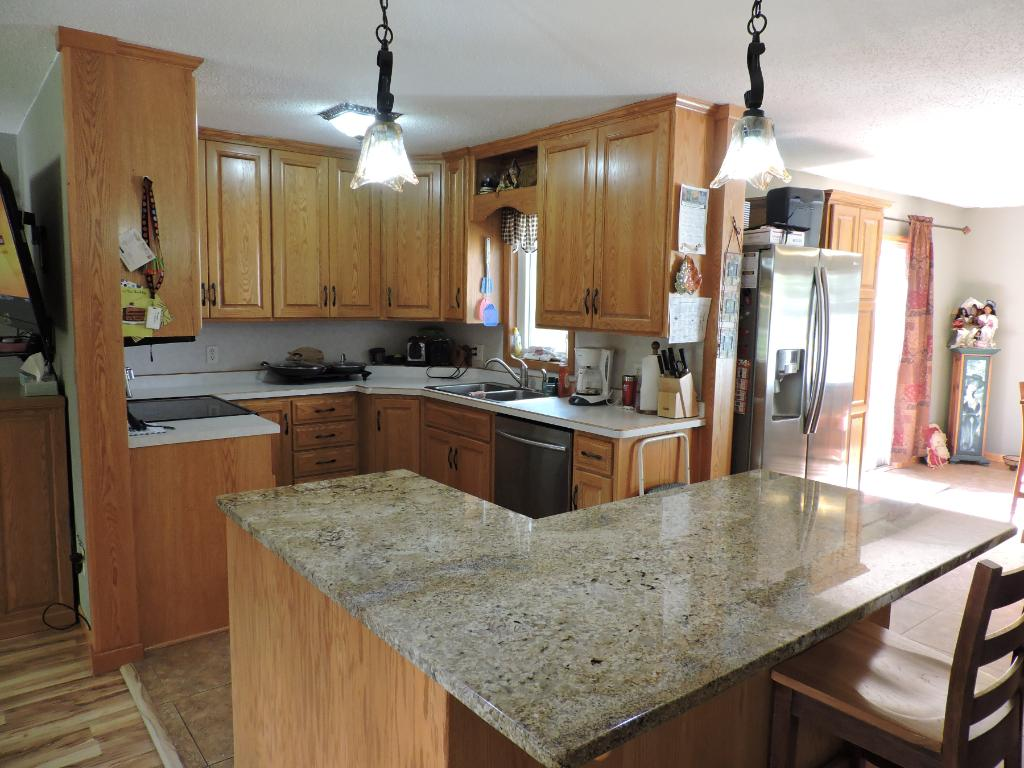 Another kitchen view w/island and granite countertops.