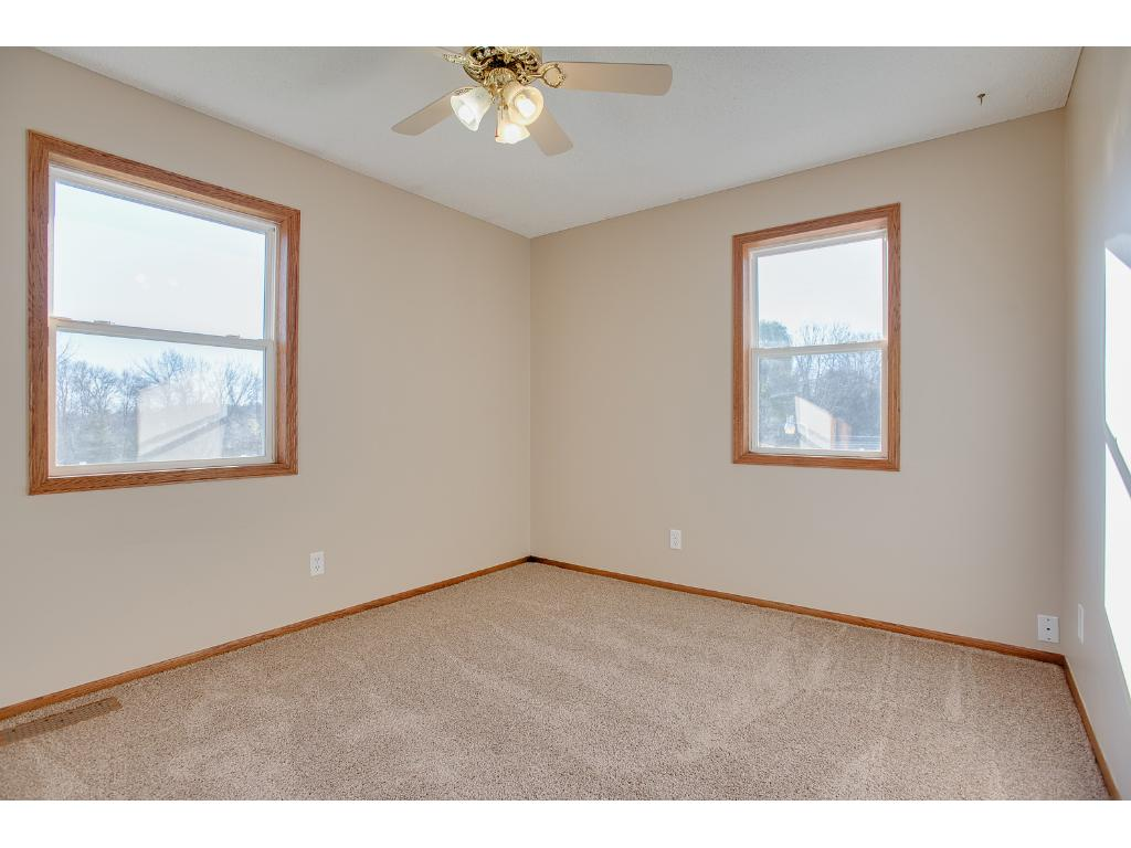 Upper level bedroom with a ceiling fan and brand new carpet