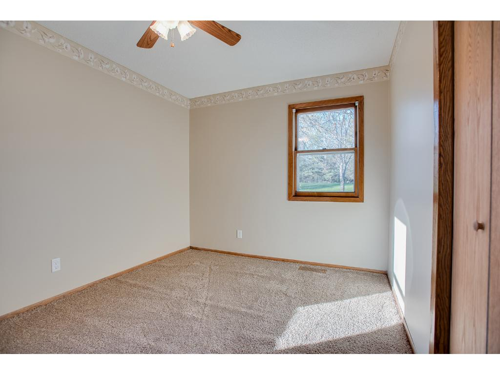 Upper level second bedroom with ceiling fan and new carpet