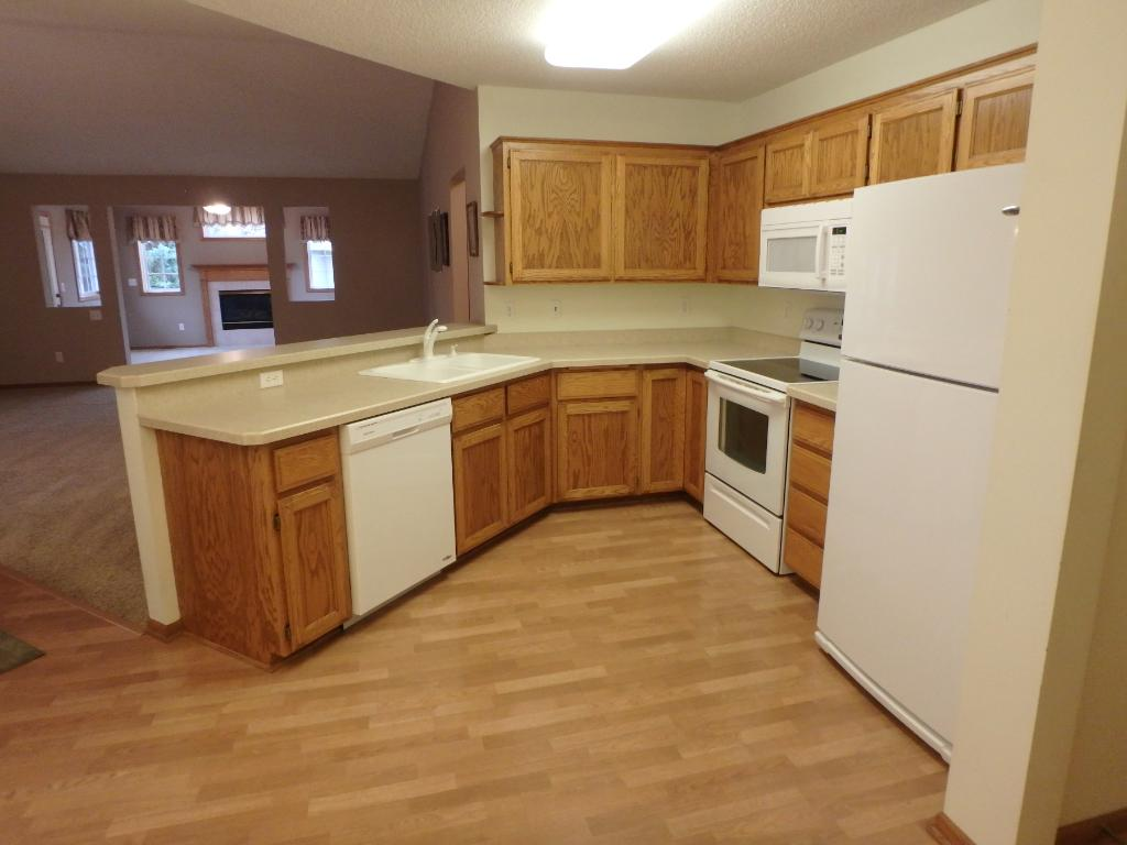Kitchen with newer laminate flooring and white appliances