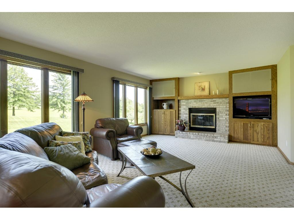Spacious family room with cozy fireplace and sweeping views of golf course...