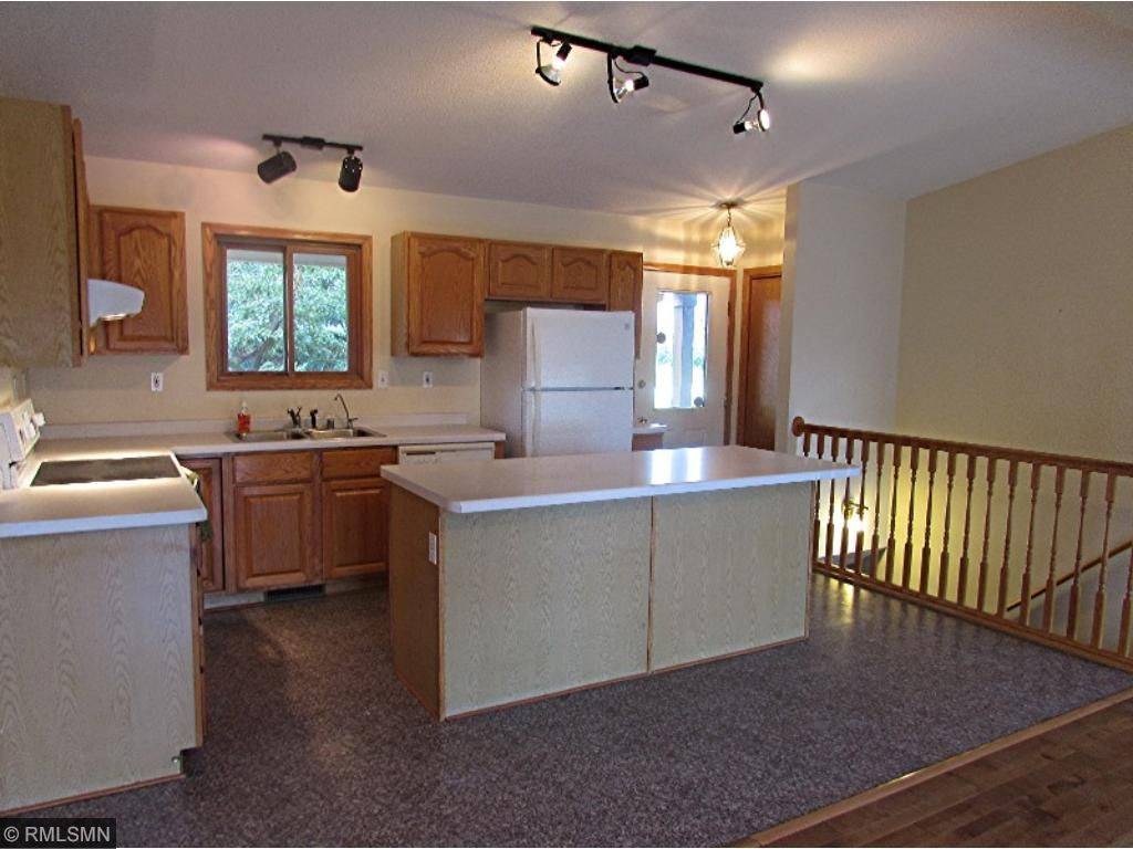 Kitchen area with entry and lower level stairway off to right side