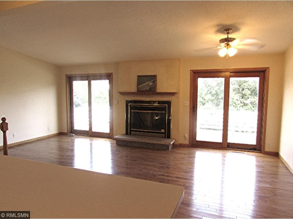 Living/Dining area with wood burning fireplace, opens to large deck overlooking lake