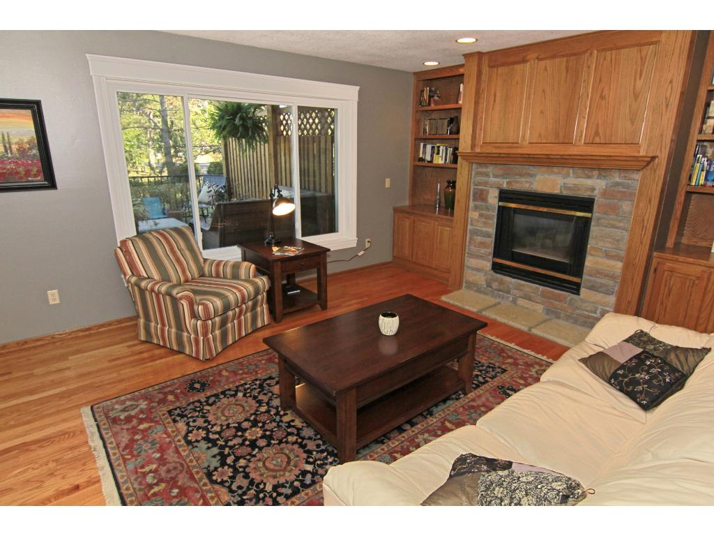 Main floor family room with gas fireplace, hardwood floors, beautiful built-ins and windows overlooking your private decks.