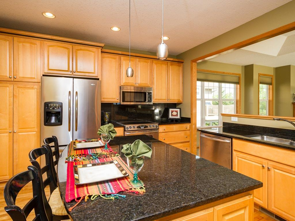 Gourmet kitchen with maple stained cabinets, granite countertops and hardwood floors.