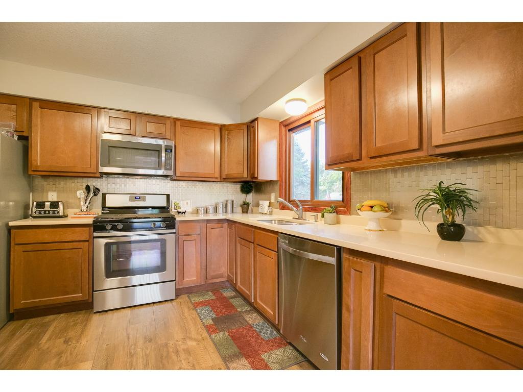 Kitchen has new cabinets, stainless steel appliances, backsplash, granite counters and engineered wood flooring!