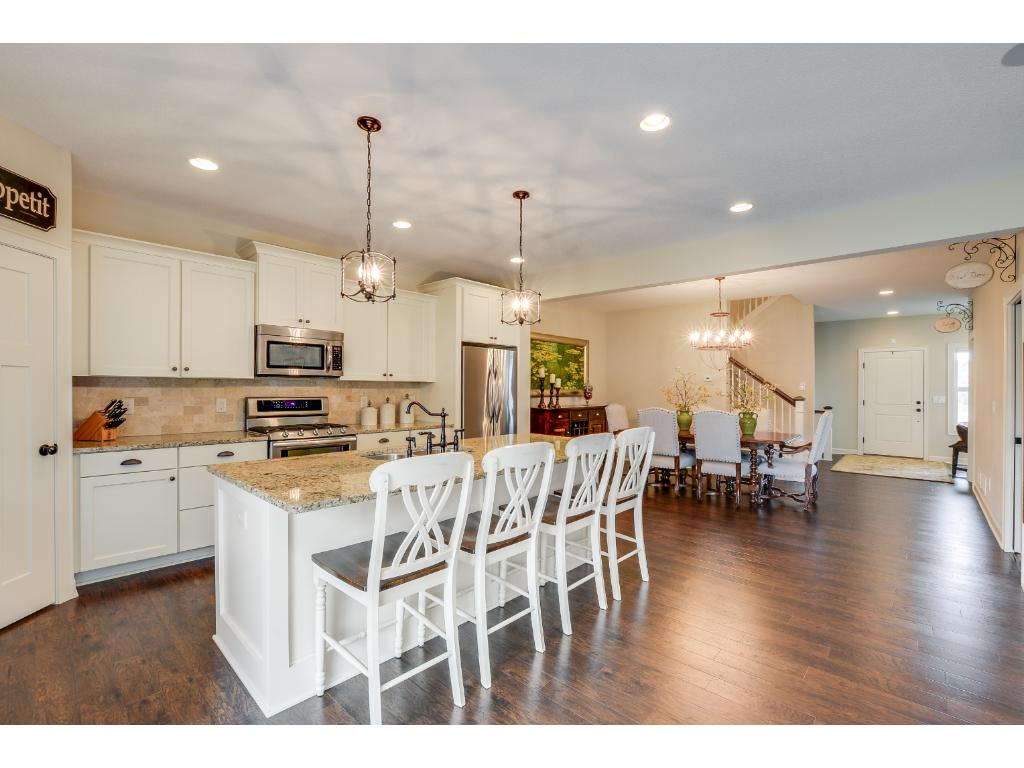 Spacious open floor plan on the main level! Stunning kitchen w/ travertine backsplash, stainless steel appliances, recessed lighting, large kitchen island w/ eat-in area, custom pendent lighting, & incredible storage space!