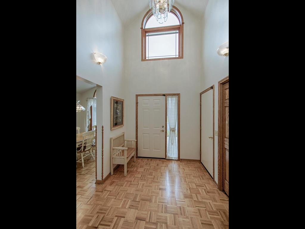 Grand foyer entrance with parkay flooring and vaulted ceilings