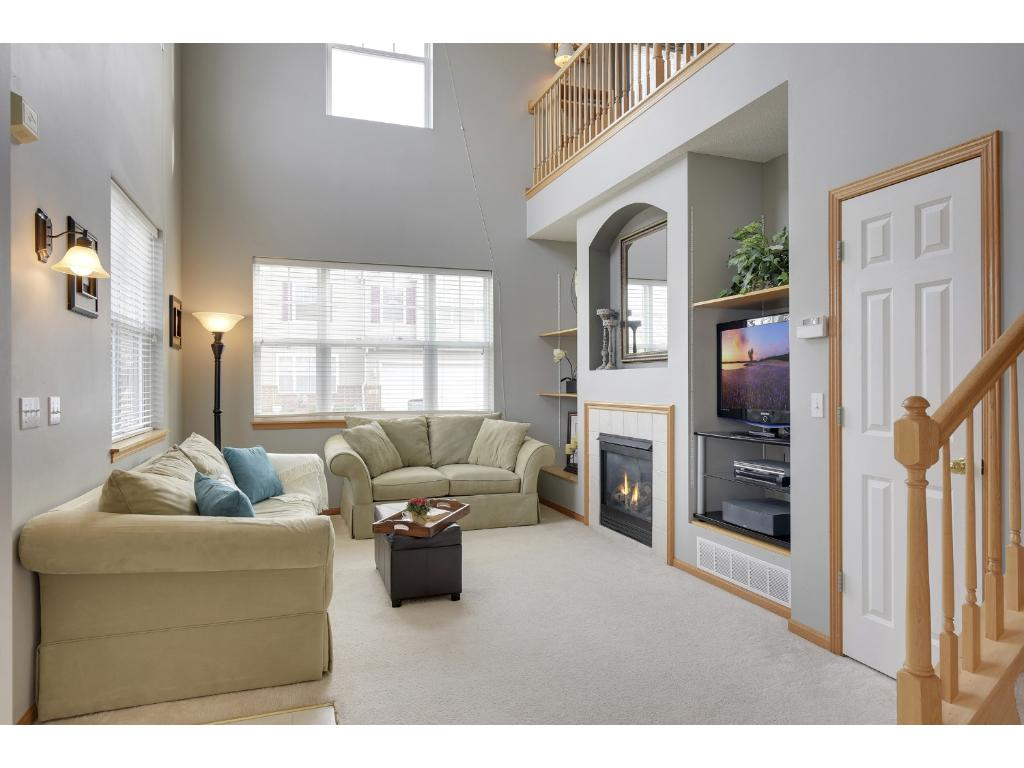 Elegant 2 story living room with gas fireplace, amazing natural light and built-ins