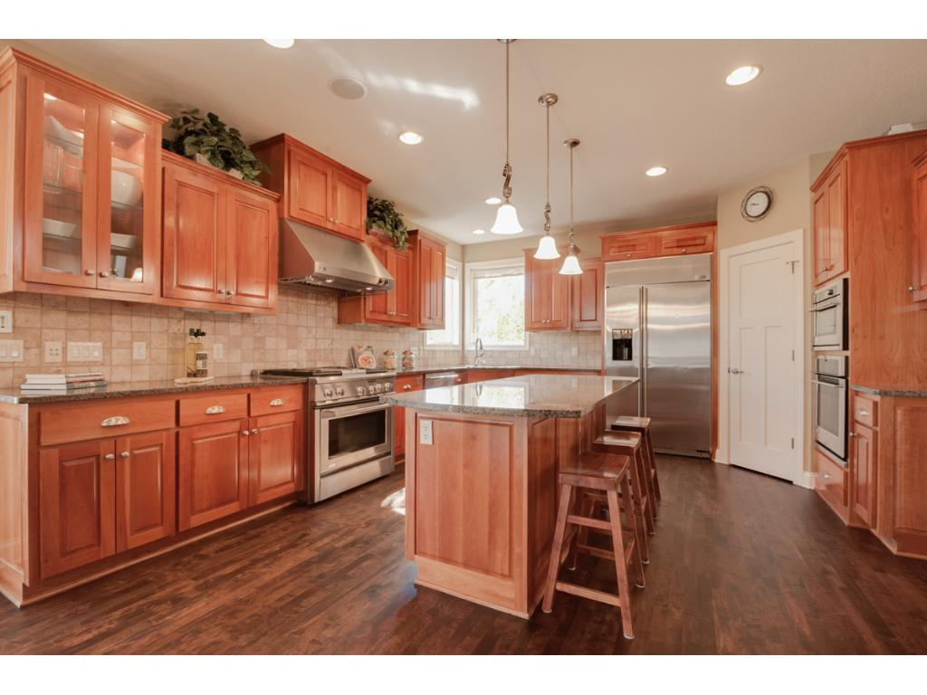 The chef's kitchen features high-end stainless steel appliances, cherry cabinetry, a large center island with wine fridge, walk-in pantry, and under cabinet lighting.