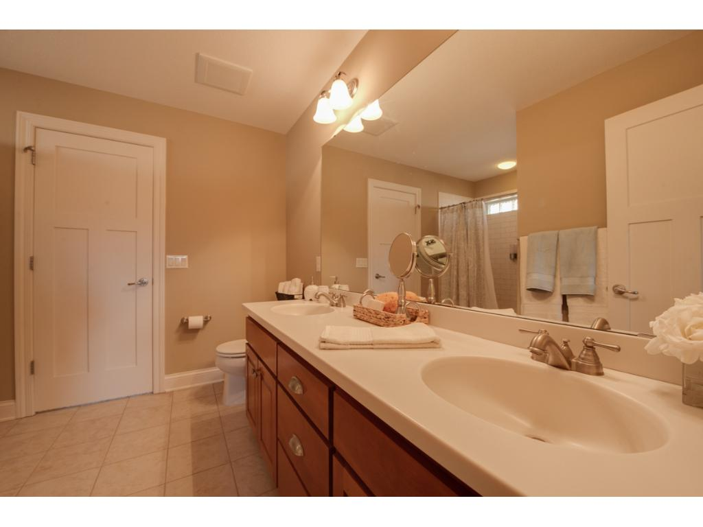 Jack and Jill bathroom with dial vanities, ceramic tile shower/tub, and tile floors.