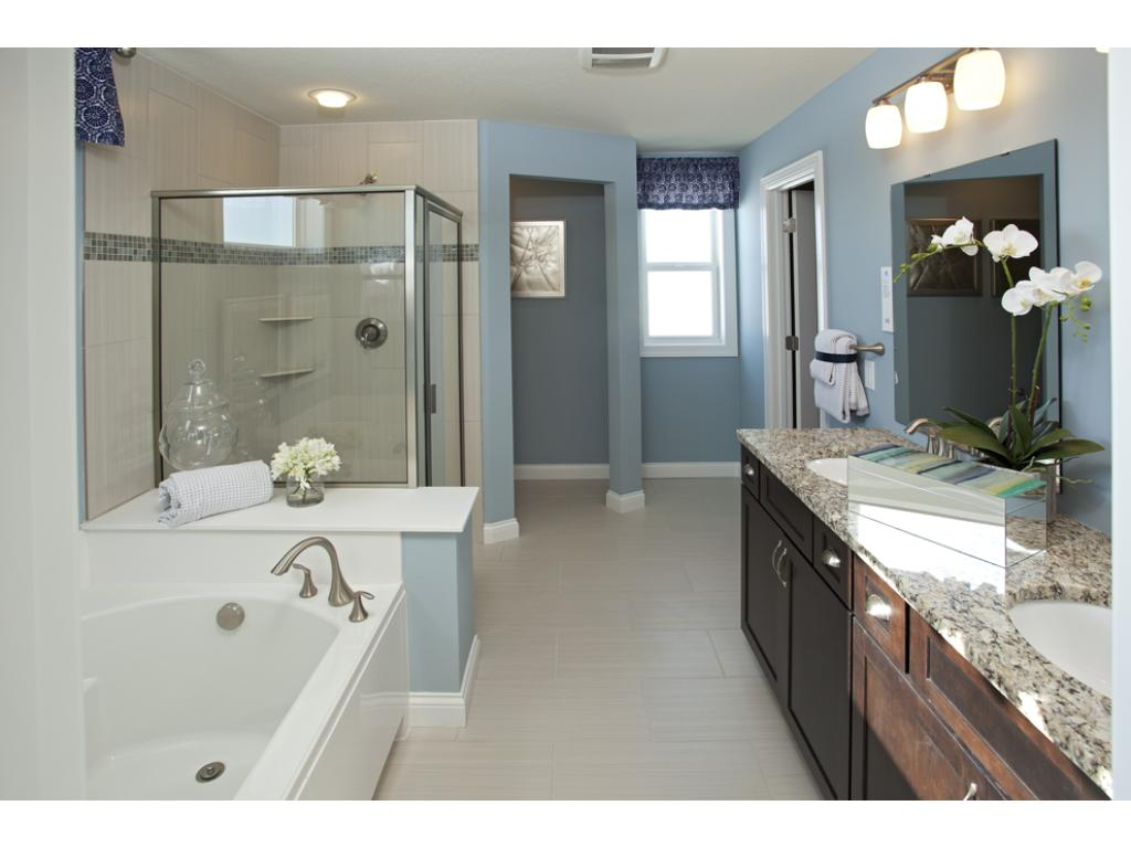 Photo of a Model Home. Owner's Bathroom with Shower and Tub.