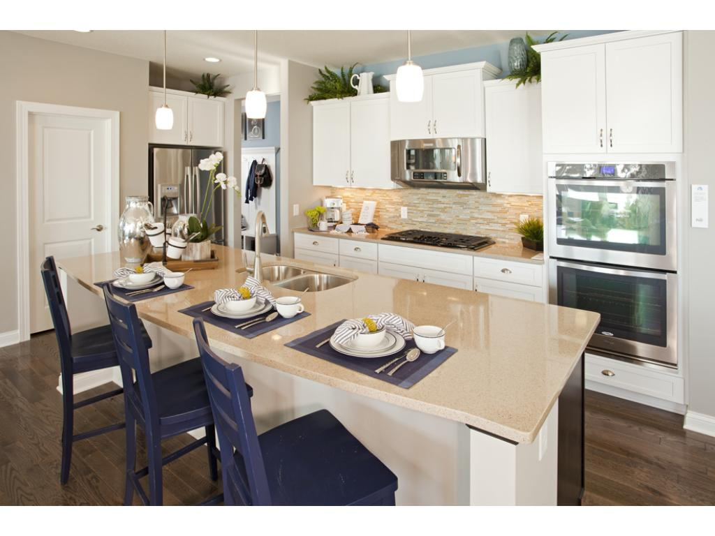 Photo of a Model Home. Gourmet kitchen with built-in stainless steel appliances.