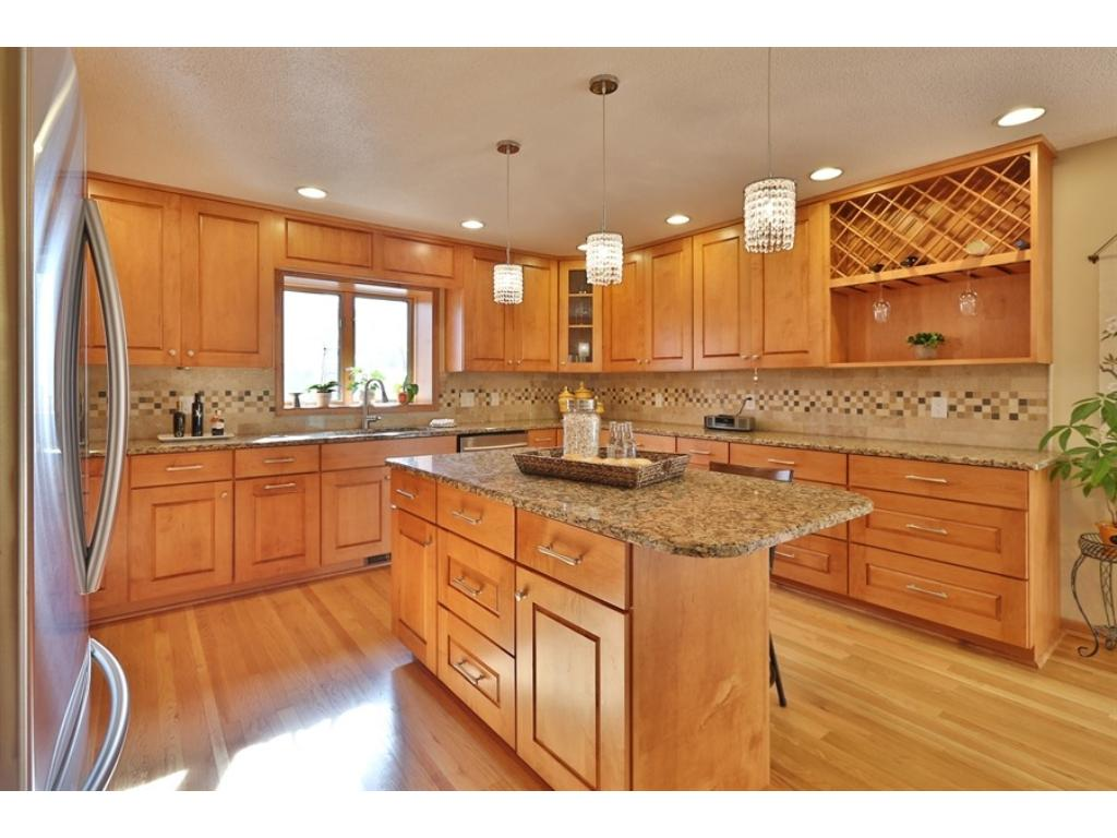 Gorgeous new center island kitchen with beautiful maple cabinetry, granite countertops, backsplash, stainless appliances and hardwood floors.