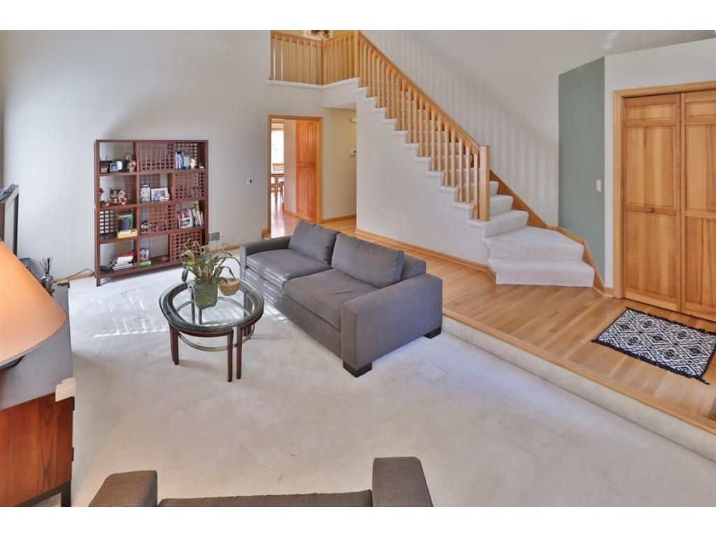 The Living Room is 2-stories tall and just off the Entry Foyer with hardwood floors.  The staircase leads up to 3 bedrooms and two renovated Baths.