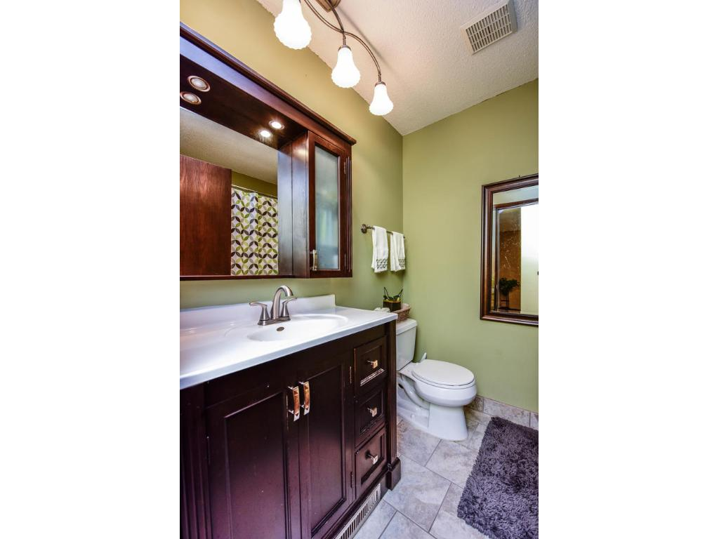 Beautifully updated main level bathroom with newer vanity, mirror, plumbing/light fixtures and flooring!