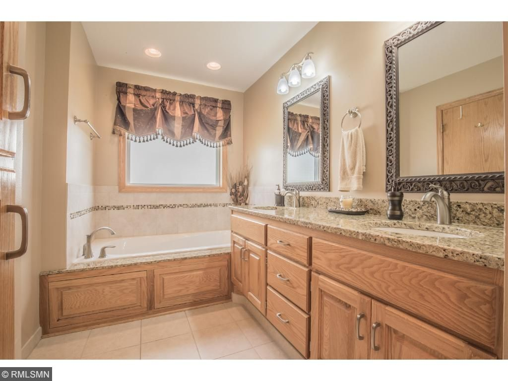 Luxurious bath with granite double sink vanity, tile flooring and shower.