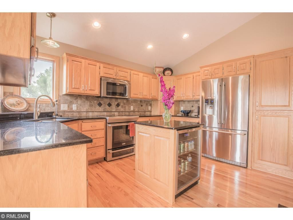 Kitchen features granite countertops, tile backsplash, stainless steel appliances, convenient appliance garage, wall pantry with pull out drawers, and center island beverage chiller.