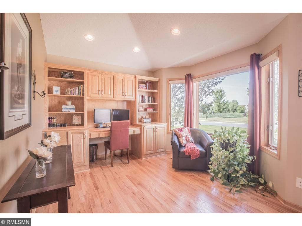 Spacious office offers custom built-ins and desk.