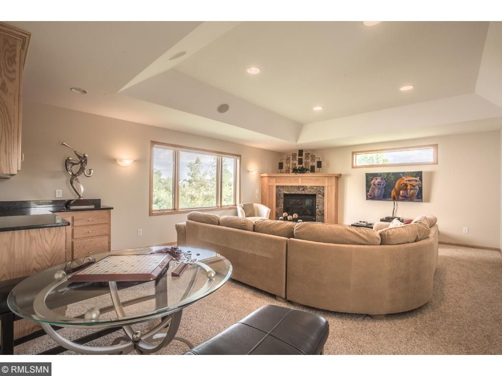 Large great room offers stunning recessed ceiling, bar, and wall of windows for grand natural light.