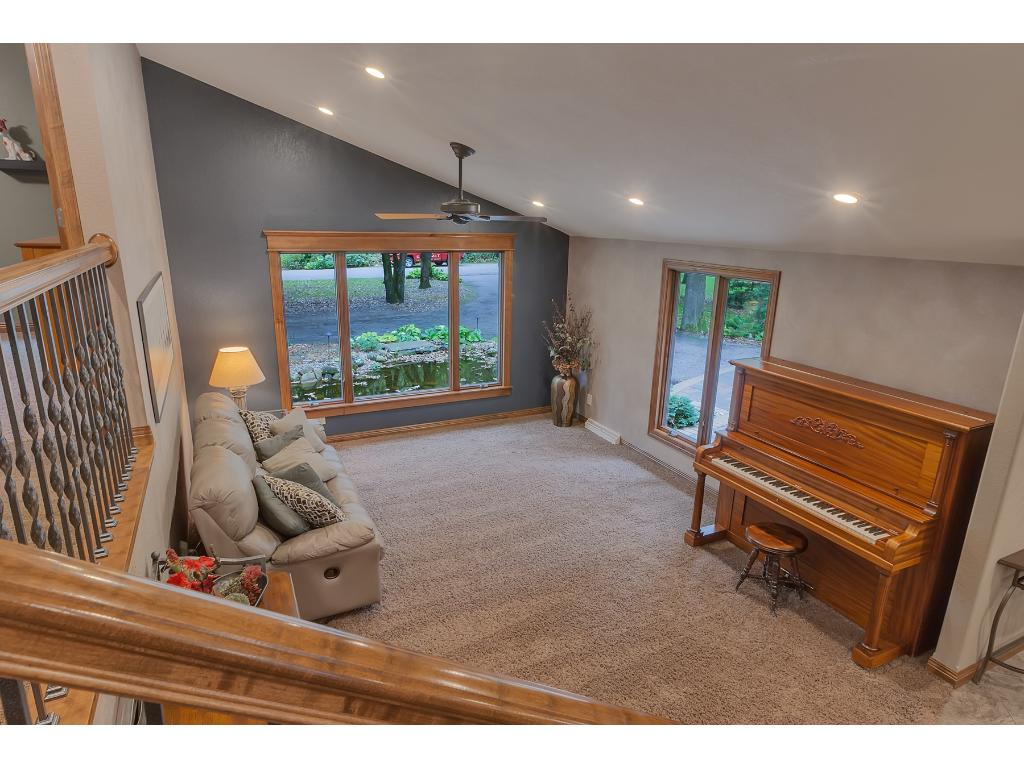 Main floor living room with vaulted ceilings, oversized windows and overlooked by the upper level walkway.