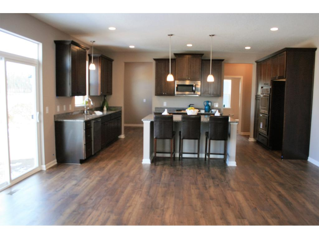 Gourmet kitchen includes buit-in double ovens and gas cooktop.  Full overlay maple cabinets all covered with granite.  Photo of similar home