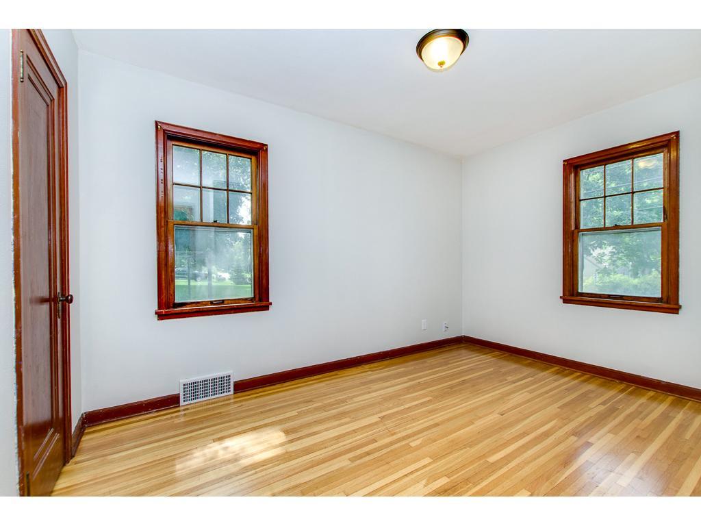 Main Floor Bedroom Featuring Original Woodwork and Hardwood Floors